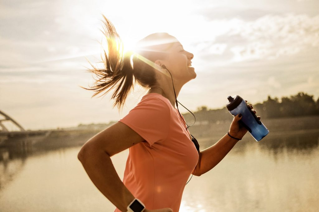 Happy woman running against morning sun